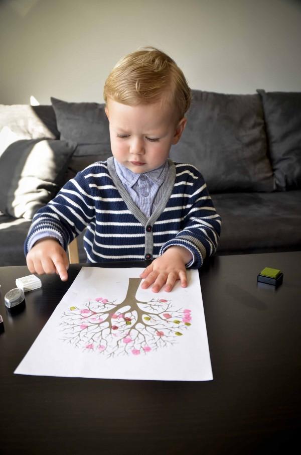 enfant qui dessine un arbre en fleur